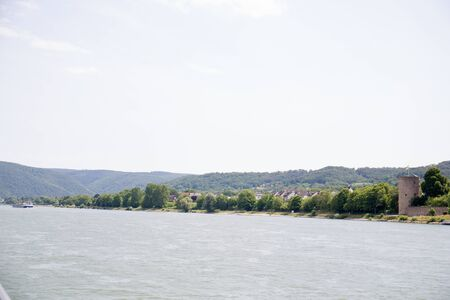 Distant view on the nature and rhine riverbank in Koblenz. Rhine and surrounding photograph during a sightseeing tour on the Rhine at a sunny day