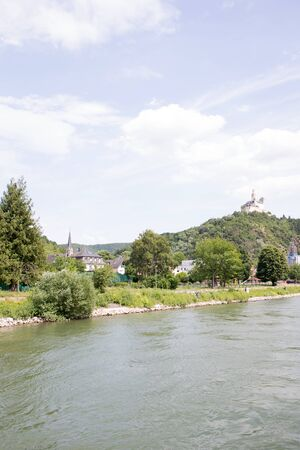 Distant view on a hill with forest on the rhine riverbank in Koblenz. Rhine and surrounding photograph during a sightseeing tour on a river on a sunny day