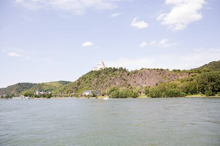 Distant view on a hill with forest on the Rhine riverbank in Koblenz. Rhine and surrounding photographed during a sightseeing tour on a river on a sunny day Stockfoto