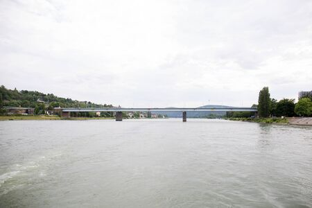 Distant view along the Rhine river and a bridge in Koblenz. Rhine and surrounding photographed during a sightseeing tour on a river on a sunny day