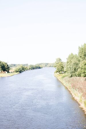 Distant view on the River Ems and the River Banks in Lathen Emsland. Germany. Photographed during a walk in the nature on a sunny day