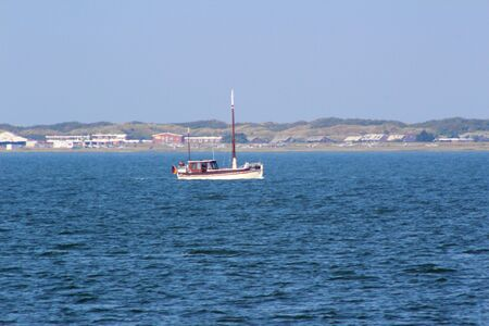 Distant view on the little boat on the northern sea island