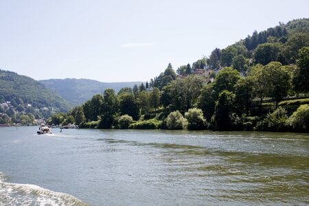View on the landscape under blue skies at the Neckar river in Heidelberg Germany during a tour by ship on the Neckar in Germany