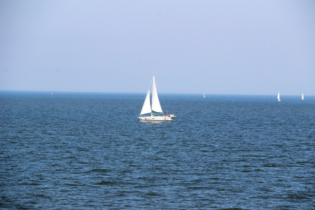 View on sail boat on the northern sea island. Young woman photographed on a sunny day Stockfoto - 132887155