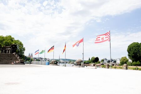 View on the flags at the Quay on the Rhine River in Koblenz. Germany under a blue sky