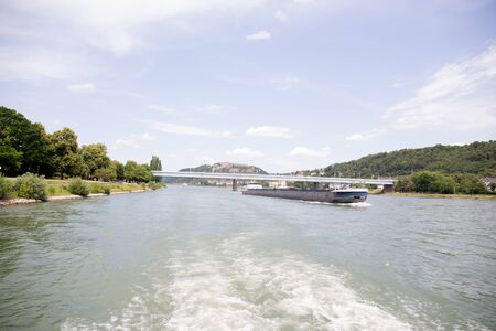 View along the Rhine river and a boat during a boat tour under blue sky