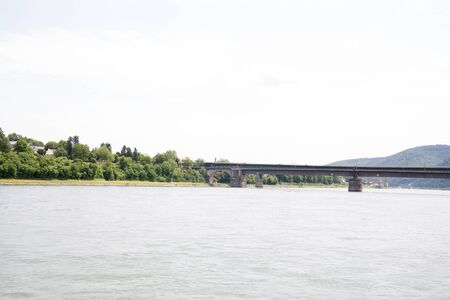 Distant view on the bridge and the natural riverbank at the rhine river in Koblenz Germany