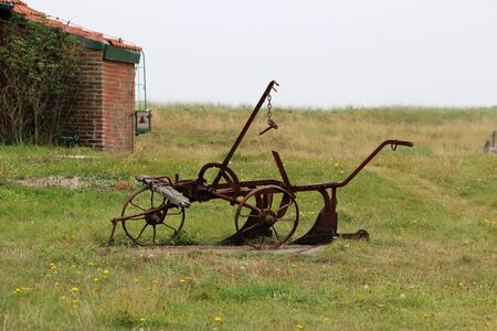 View on an old plow on a grass area at the northern sea island juist germany