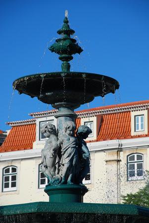 Baroque style bronze fountain on Rossio square in Lisbon, Portugal. Rossio Square is the popular name of the Pedro IV Square (Portuguese: Praca de D. Pedro IV) in the city of Lisbon, in Portugal