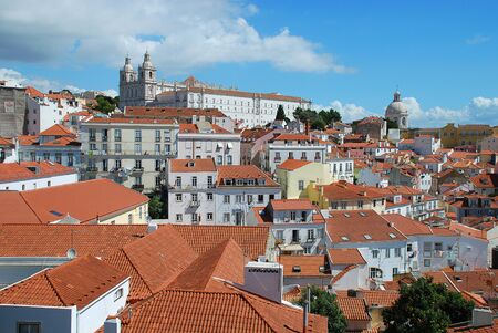 Sao Vincente de Fora church above the red rooftops of the houses in the center of Lisbon Stock Photo