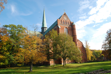 Minster in Bad Doberan (Germany), autumn trees with yellow leaves in the park of the church