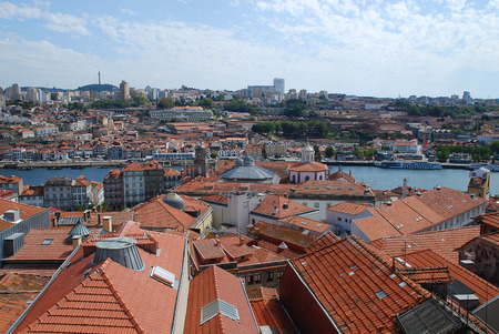Colored facades and roofs of houses in Porto and the river Douro, Portugal. Porto is the second-largest city in Portugal after Lisbon