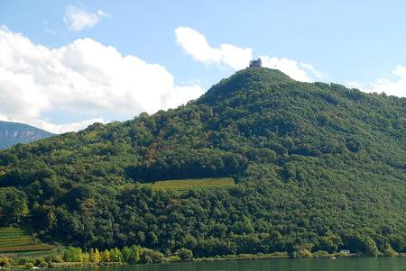 Small ruin on the top of the mountain, Lake Kaltern, Lago di Caldaro. Lake Kaltern (Italian: Lago di Caldaro; German: Kalterer See) is a lake in the municipality of Kaltern in South Tyrol, Italy Foto de archivo