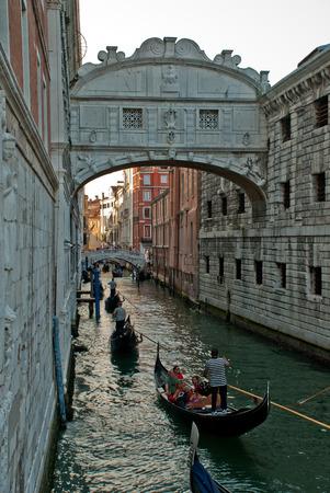Venice, Italy: Gondola on small canal passing towards famous Bridge of Sighs (Ponte dei Sospiri), view from Ponte della Paglia at  Rio di Palazzo