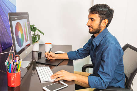 Side view. Young bearded businessman in denim shirt is sitting in office at table and is using computer with color swatch on screen. On table is smartphone and stationery. Man working Banco de Imagens