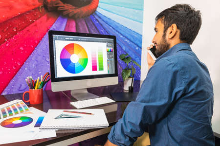 Side view. Young bearded businessman in denim shirt is sitting in office at table. Using his smartphone while looking at color swatch.