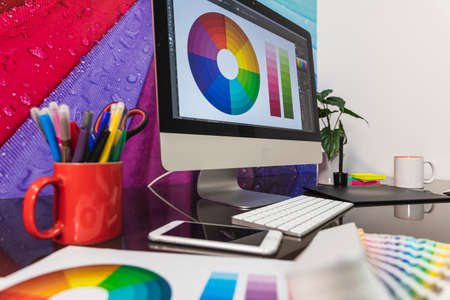 Modern graphic designer office workplace with digital tablet, notepad, colorful pencils, cellphone. Some Color swatch samples over modern desk