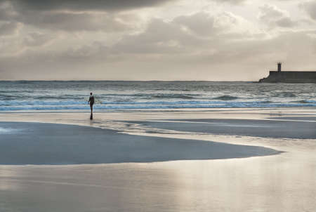 image created 21st century: Surfer walking  to the sea at sunset