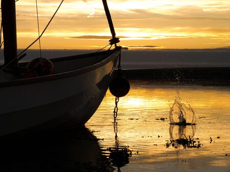 estuary: A boat in the estuary at sunset with a splash