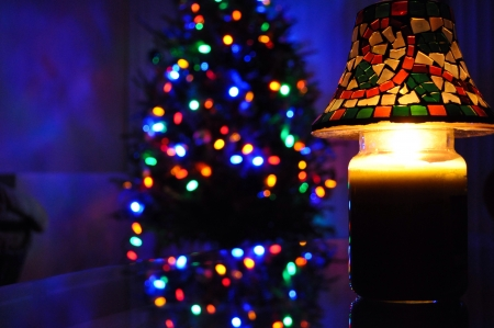 Christmas candle and a beautiful decorated Christmas tree in the background. Stock Photo - 23437194