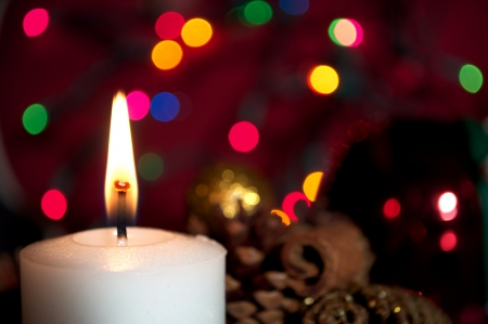 A burning white Christmas Candle with decorations and colorful christmas lights in the background   Stock Photo