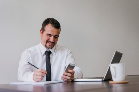 Positive senior menager holding smartphone and writing notes. Banque d'images