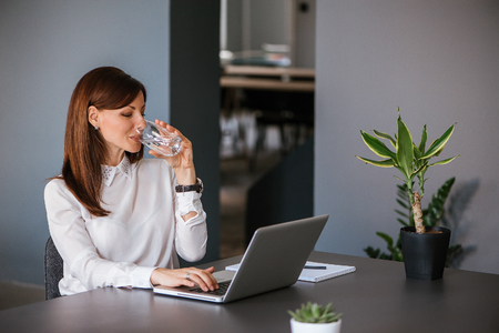 Stay hydrated. Pretty young woman in the office drinking water while working. Drinking from glass.