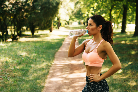 drinks after work: Ftness athlete woman drinking water after work out exercising outdoor.