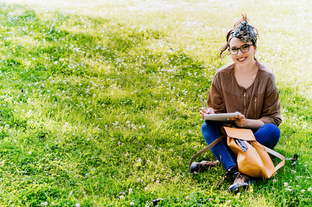educacion ambiental: Beautiful woman with glasses writing into her diary, in the park.