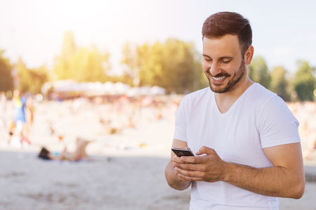 Young man typing on a mobile phone, beach background
