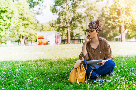 Thoughtful woman writing on paper in park