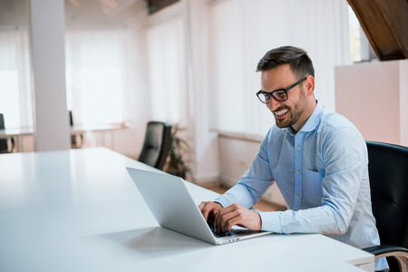 Happy young businessman using laptop at his office desk.