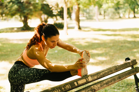 Woman stretching leg on bench before exercise Stock Photo