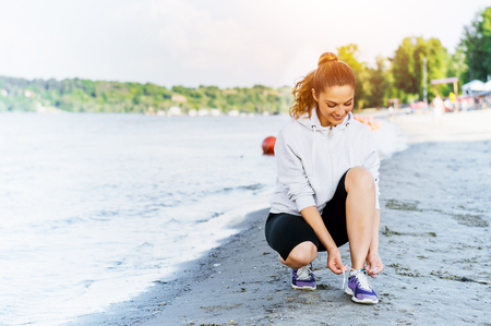 Woman tying laces before training on beach. Stock Photo