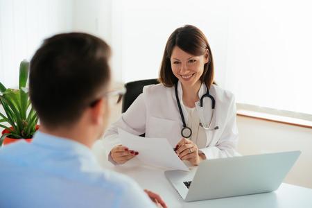 Lächelnde Ärztin, die medizinische Ergebnisse an männliche Patienten berichtet. Standard-Bild - 85098328