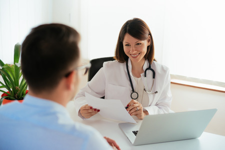 Smiling female doctor reporting medical results to male patient. Banque d'images