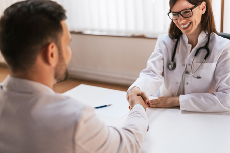 Smiling doctor at the clinic giving an handshake to his patient