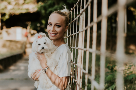 Young casually dressed woman holding her adorable maltese puppy