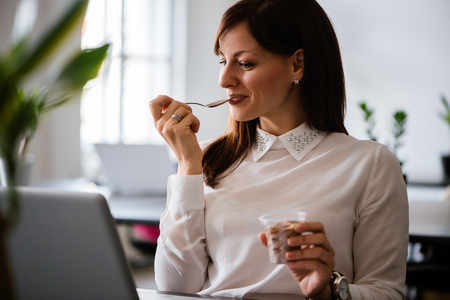 Portrait of a pretty businesswoman sitting in the office with a laptop using wireless internet, having dessert after lunch