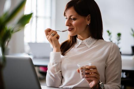 Ritratto di una bella donna d'affari seduto in ufficio con un computer portatile tramite internet wireless, con dessert dopo pranzo Archivio Fotografico - 96236017