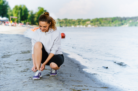 Woman lacing sport shoes and getting ready for running and exercising at beach