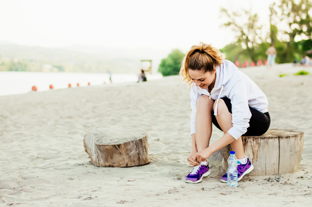 Runner woman tying laces of running shoes preparing for beach jogging. Stock Photo