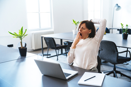 Young business woman yawning at a modern office desk in front of laptop.