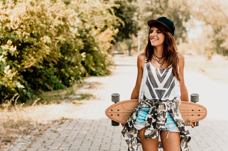 Smiling young woman portrait holding long board.