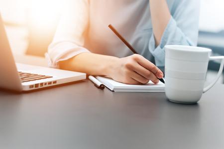Hand van onderneemster die op papier in het bureau schrijft.