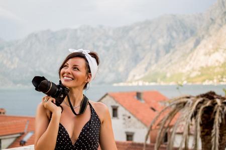Beautiful stylish woman holding camera outside.