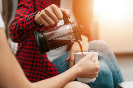 De gietende koffie van de vrouw aan haar vriend, sluit omhoog. Stockfoto