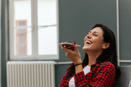 Woman laughing while talking on speakerphone. Stockfoto