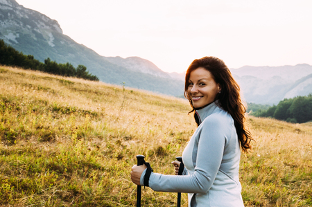 Smiling hiker girl walking in country path Stock Photo