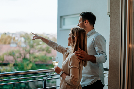 Young couple enjoy drinking wine at balcony. Woman pointing at something. Stockfoto